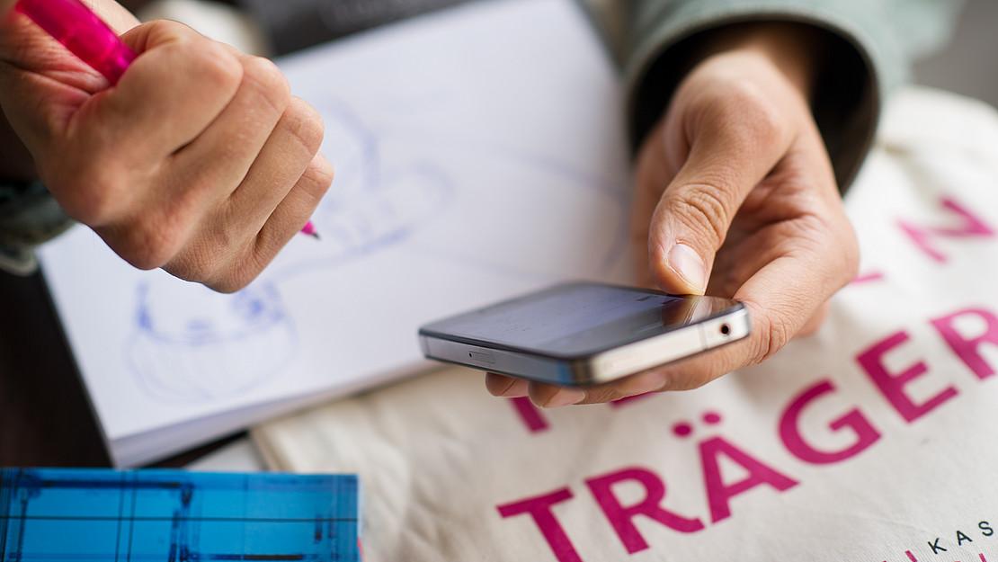 Hände mit Smartphone und Schreibblock