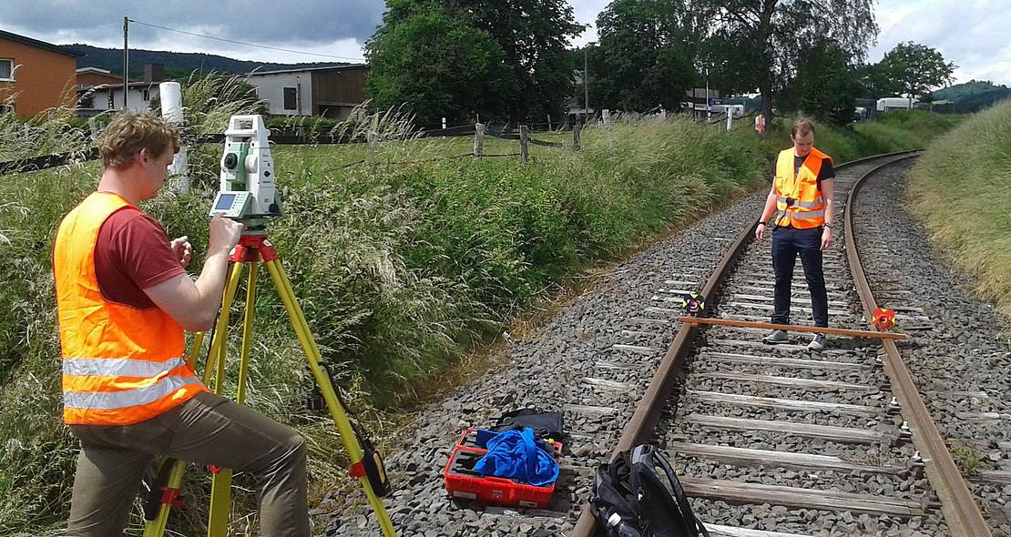 Zwei Studenten stehen in Sicherheitskleidung und mit Vermessungstechnik an einer Kleinbahnstrecke