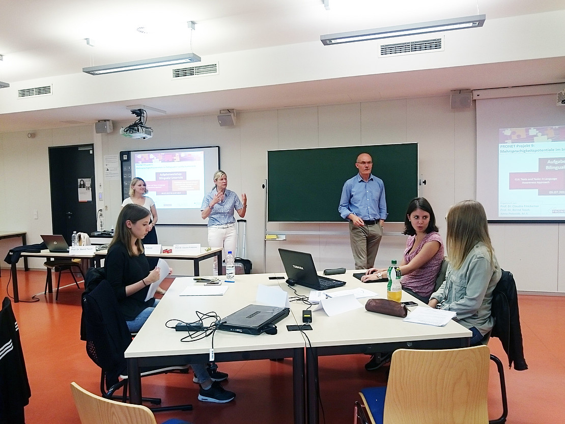 Bild zeigt Seminarraum mit 6 Personen. 3 Personen stehen vor Projektion bzw Tafel, 3 Personen sitzen an einem Gruppentisch